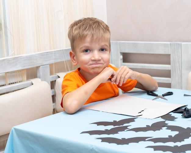 Un ragazzo disegna e taglia una decorazione di halloween a casa da carta nera. decorazioni artigianali fai da te. il bambino fa i pipistrelli neri di carta, origami