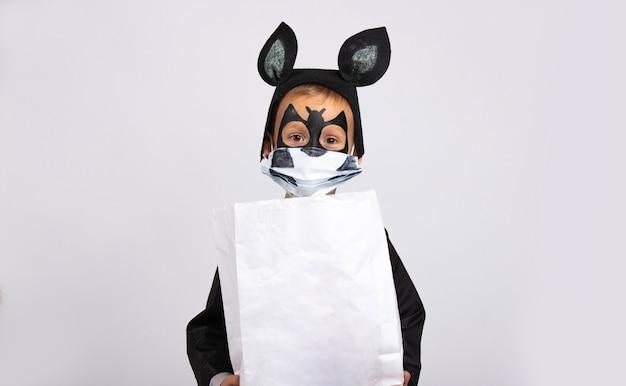 Ragazzo vestito come un pipistrello che tiene un sacchetto di caramelle bianco con uno spazio vuoto. il virus ha attaccato il mondo.