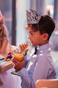 Ragazzo che beve succo di frutta a una festa di compleanno