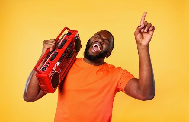 Il ragazzo ascolta la musica con un vecchio stereo e balla. espressione emotiva ed energetica. muro giallo