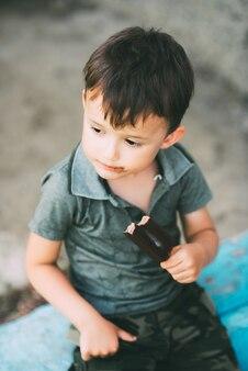 Il ragazzo mangia il gelato su un bastone ricoperto di cioccolato, carino all'aperto