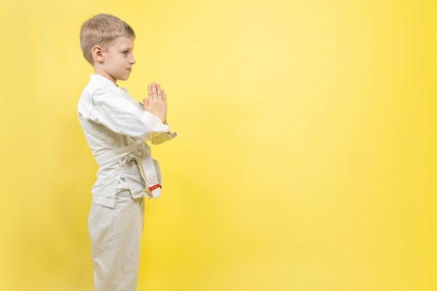 Ragazzo impegnato nel karate su un muro giallo. lezioni di judo, stile di vita sportivo aikido.