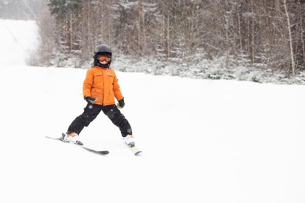 Un ragazzo in attrezzatura sta sciando su un pendio innevato
