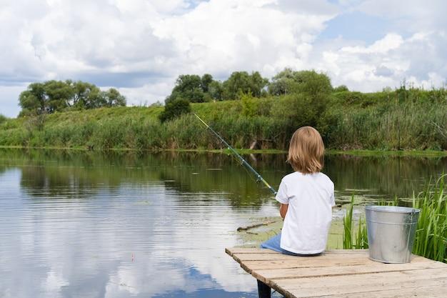 Ragazzo che pesca su un ponte di legno vicino a uno stagno