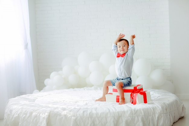 Il ragazzo si diverte e gioca nella stanza sul letto con un lenzuolo bianco