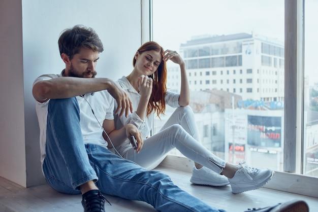 Ragazzo e ragazza che chiacchierano insieme vicino alla finestra degli appartamenti. foto di alta qualità