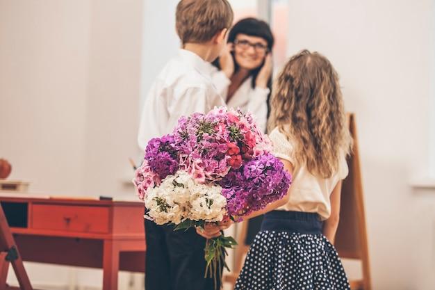 Bambini maschi e femmine regalano fiori come insegnante di scuola durante la giornata dell'insegnante