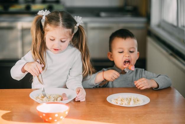 Ragazzi e ragazze in cucina che mangiano salsicce con la pasta è molto divertente e amichevole