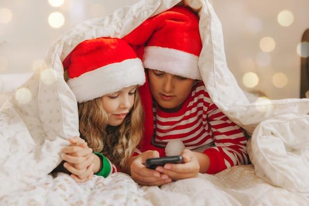 Un ragazzo e una ragazza con i cappelli di natale giacciono sotto le coperte con gli smartphone in mano. capodanno e natale
