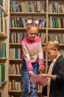 Ragazzo e ragazza che parlano di libro in biblioteca scolastica, stili di vita di persone e amico concetto di educazione e amicizia. tempo libero per bambini, attività di gruppo
