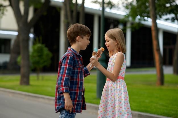 Ragazzo e ragazza si scambiano il gelato, appuntamento per bambini