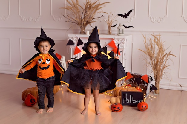 Ragazzo e ragazza in costume da strega di halloween con la zucca