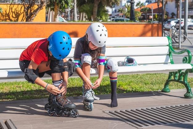 Ragazzo e ragazza che mettono sui pattini a rotelle all'aperto