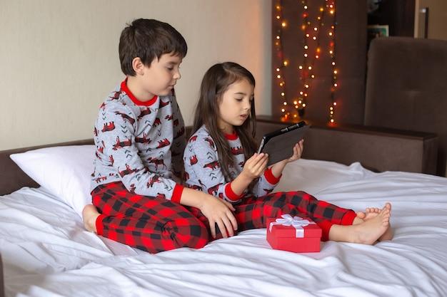 Un ragazzo e una ragazza in pigiama rosso e grigio sono seduti a casa sul letto, guardando con calma una digitale
