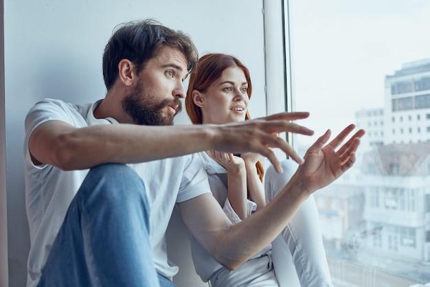 Ragazzo e ragazza seduti sul davanzale della finestra gioia romantica