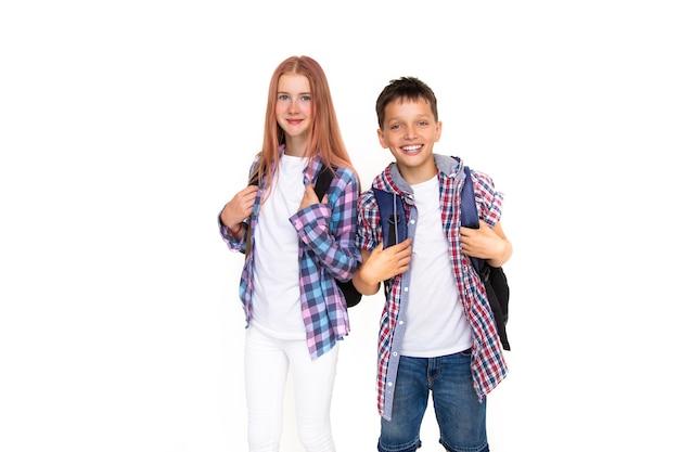 Ragazzo e ragazza adolescente 11 anni scolaro e studentessa che guarda l'obbiettivo su priorità bassa bianca con lo zaino e sorridente. vestito con camicia a quadri e camicia bianca