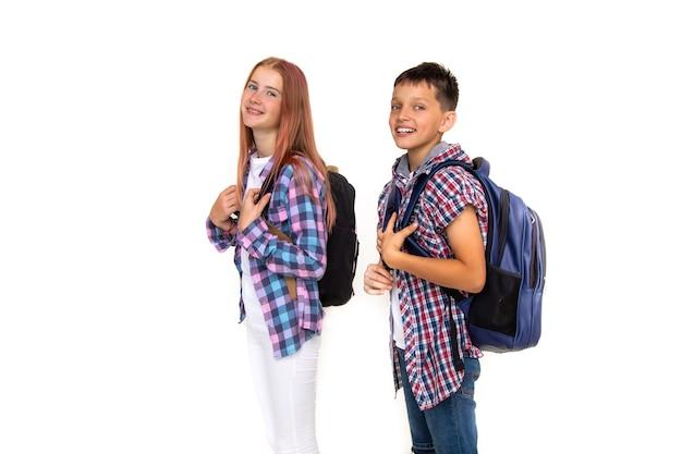 Ragazzo e ragazza adolescente 11 anni scolaro e studentessa che guarda l'obbiettivo su priorità bassa bianca con zaini e sorridente. vestito con camicia a quadri, camicia bianca
