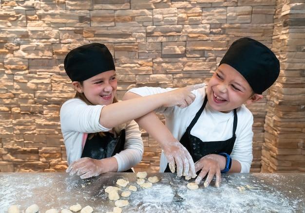 Ragazzo e ragazza gemelli che giocano mentre cucinano con la farina in abiti da chef
