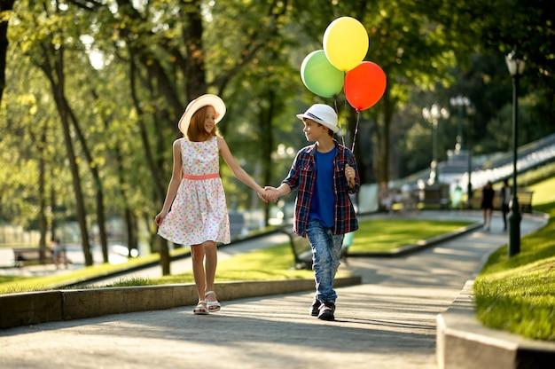 Ragazzo e ragazza che camminano con le mongolfiere nel parco