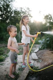 Ragazzo e ragazza che innaffiano il giardino in summe