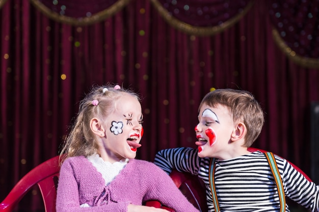 Ragazzo e ragazza che indossano il trucco da clown seduti su una sedia fianco a fianco e si fanno la lingua l'un l'altro