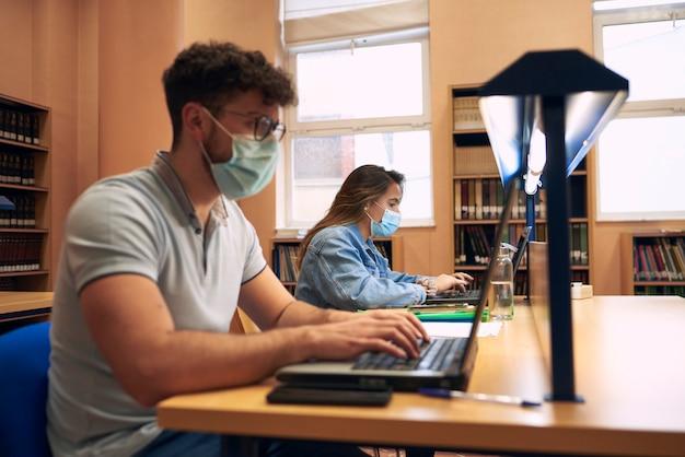 Un ragazzo e una ragazza che indossano maschere usano i laptop nella biblioteca