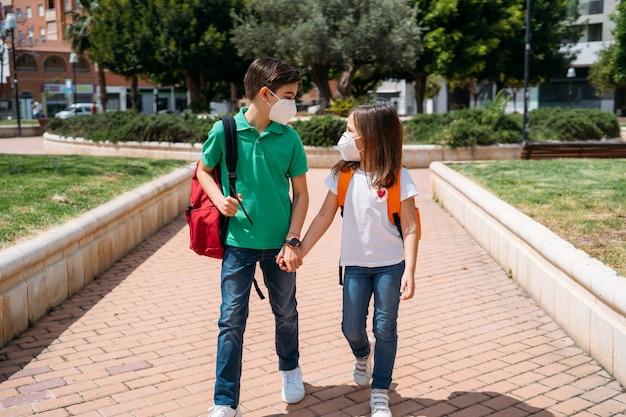 Ragazzo e ragazza con zaini e maschere che vanno a scuola nella pandemia di coronavirus
