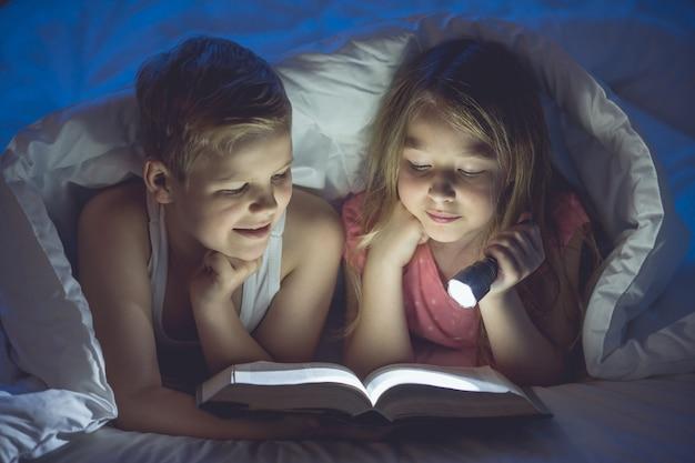 Il ragazzo e la ragazza con un libro e una torcia erano al coperto. notte