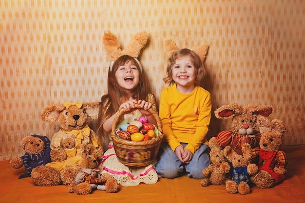 Ragazzo e ragazza con orecchie di coniglio seduti intorno un sacco di paglia e lepri peluche, stile vintage.