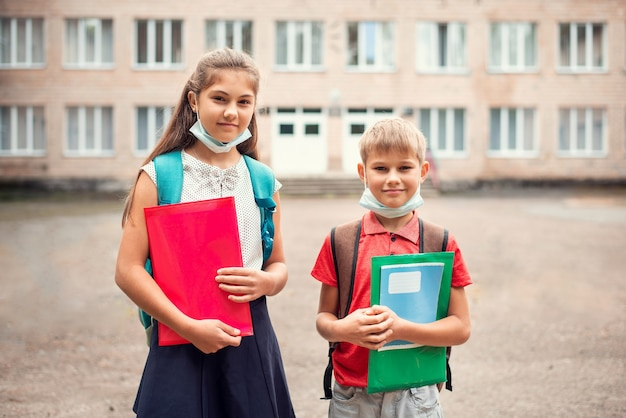 Ragazzo e ragazza con le borse di scuola che indossano maschere mediche sotto il mento e che tengono i materiali di apprendimento