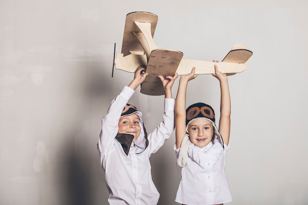 Ragazzo e ragazza con aereo modello in legno e un berretto con cappuccio