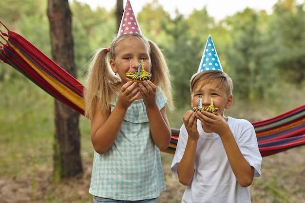 Ragazzo e ragazze che festeggiano il compleanno all'aperto in giardino