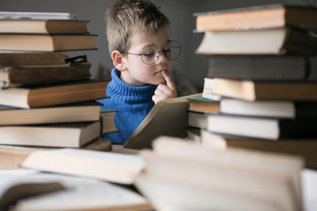 Ragazzo con gli occhiali che legge un libro con una pila di libri accanto a lui.