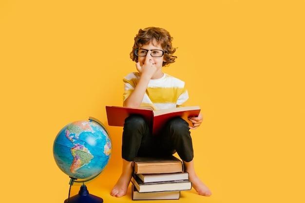 Ragazzo con gli occhiali si siede su una pila di libri, vicino al globo