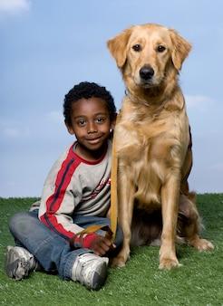Ragazzo e un golden retriever che si siedono sull'erba contro un cielo blu