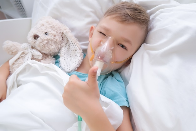 Il ragazzo ha l'inalazione, procedura per il trattamento dei polmoni.