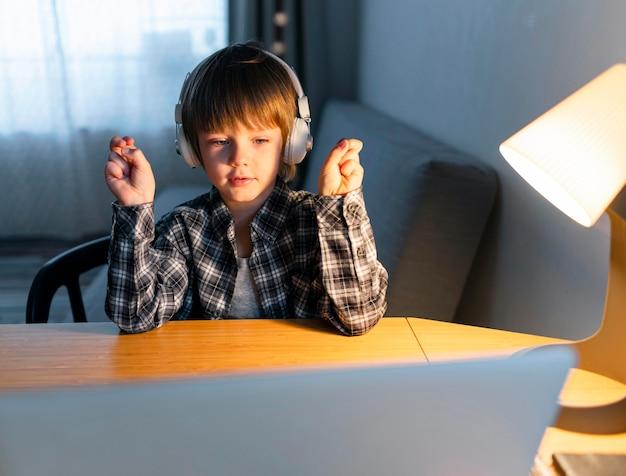 Ragazzo che ha corsi virtuali sul laptop e citando