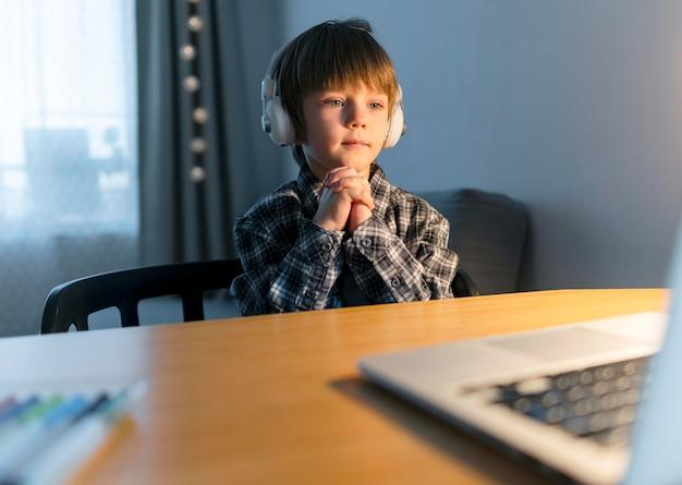 Ragazzo che ha corsi virtuali sul computer portatile