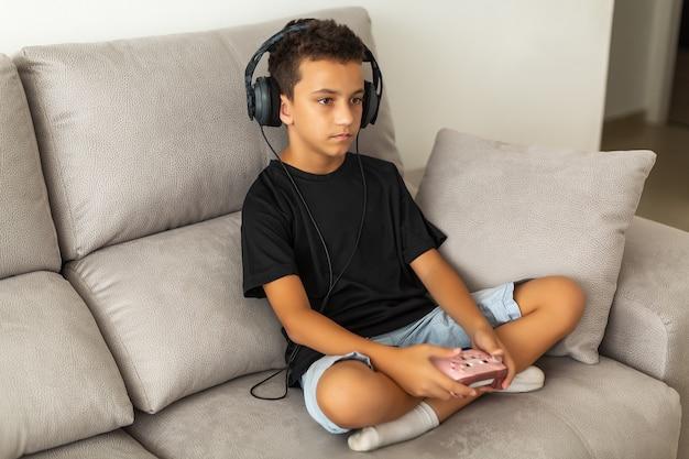 Ragazzo in cuffie che gioca video gioco sul divano
