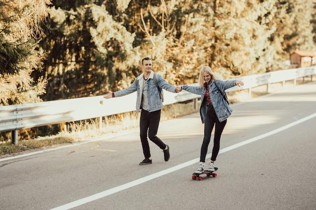 Ragazzo che aiuta la sua ragazza a guidare uno skateboard sulla strada in montagna.