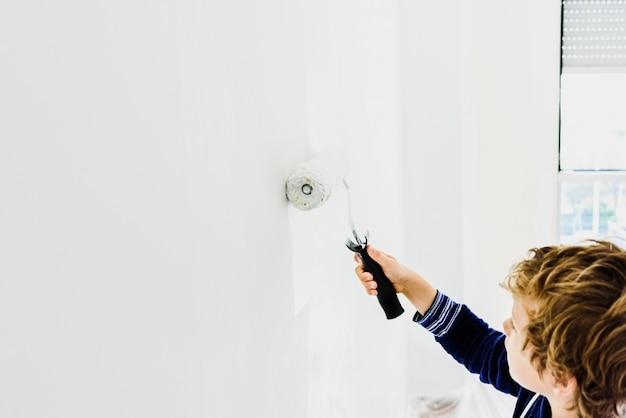 Il ragazzo aiuta la sua famiglia a dipingere un muro bianco.