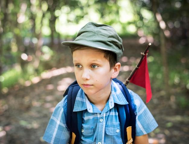 Ragazzo che fa un'escursione attraverso una foresta