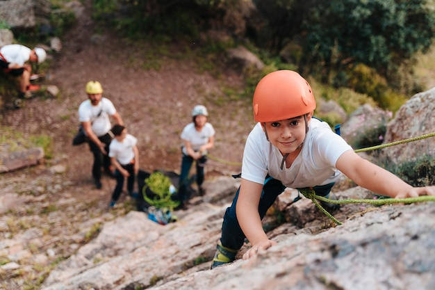 Ragazzo di 10 anni che si arrampica mentre i suoi coetanei lo guardano dal basso. copia spazio.