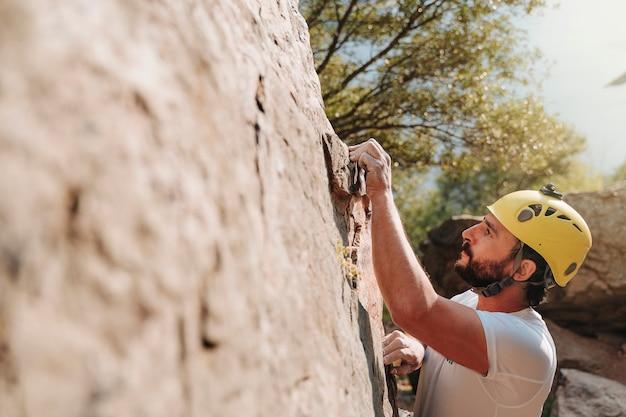 Ragazzo sulla trentina che tiene in mano una roccia mentre si arrampica. copia spazio