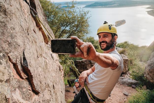 Ragazzo sulla trentina che si fa un selfie mentre si arrampica