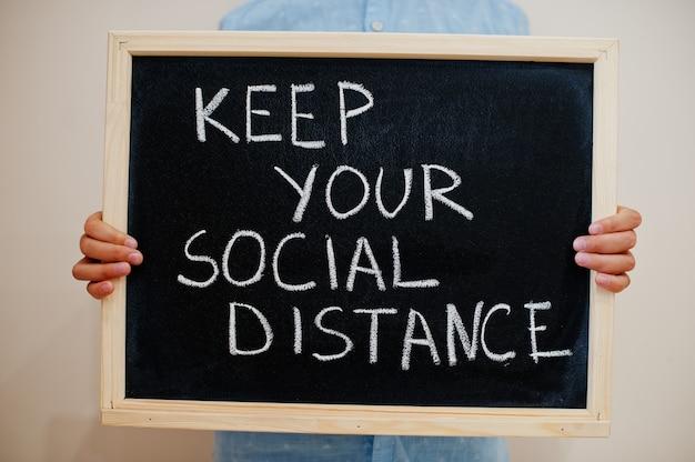 Ragazzo tenere l'iscrizione alla lavagna con il testo mantieni la distanza sociale
