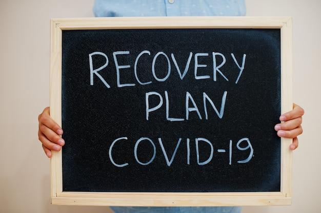 Ragazzo tieni l'iscrizione alla lavagna con il testo recovery plan covid-19