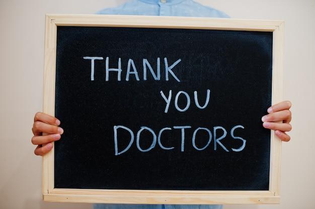 Ragazzo tenere l'iscrizione alla lavagna con il testo grazie, dottori