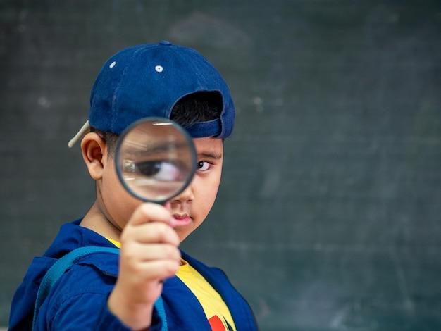 Il ragazzo che tiene la lente d'ingrandimento davanti alla lavagna. di nuovo a scuola.