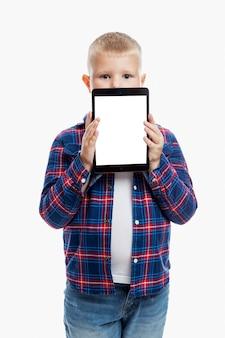 Compressa della tenuta del ragazzo con lo schermo isolato su bianco. bambino 6-7 anni. informazione e comunicazione. verticale.
